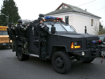 Seattle Police Department SWAT team officers leave the scene of an all night stakeout in Seattle