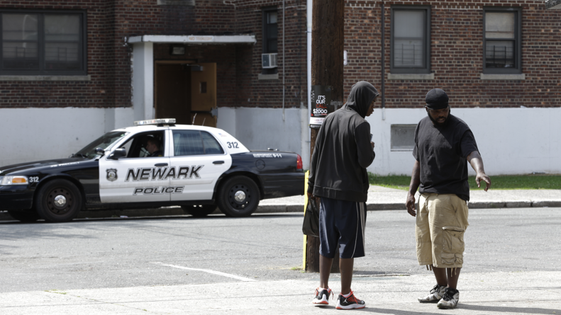 Two men talk at the scene where a day earlier a 14-year-old boy was killed as a Newark Police Department officer sits in a police vehicle, Thursday, Sept. 5, 2013, in Newark, N.J.  (AP Photo/Julio Cortez)