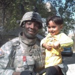 U.S. Army infantry squad leader Isiah James poses with a boy in Baghdad, Iraq, during his first deployment to the region between 2006 and 2008
